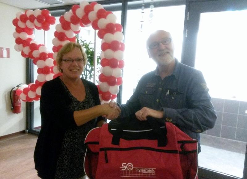 Voorzitter Harrie Harperink overhandigt een nieuwe sporttas aan lid van de vereniging Henriette Hensema